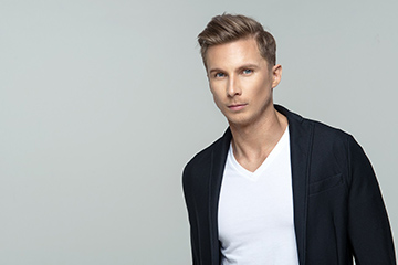 Elegant blonde man standing in studio against cool grey background