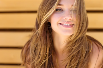 Woman smiling into the camera whilst her hair blows