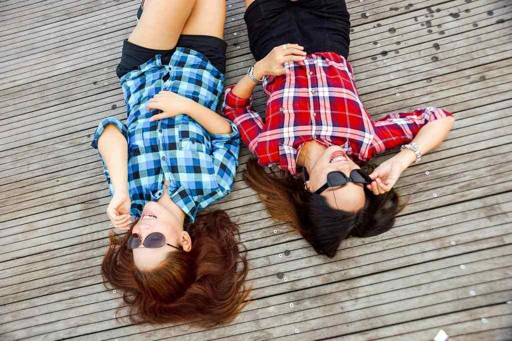 Two girls lying back on a deck smiling