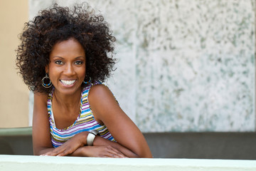 Black woman smiling into the camera against a grey background