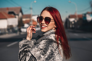 Woman with red hair and sunglasses smiling into the camera