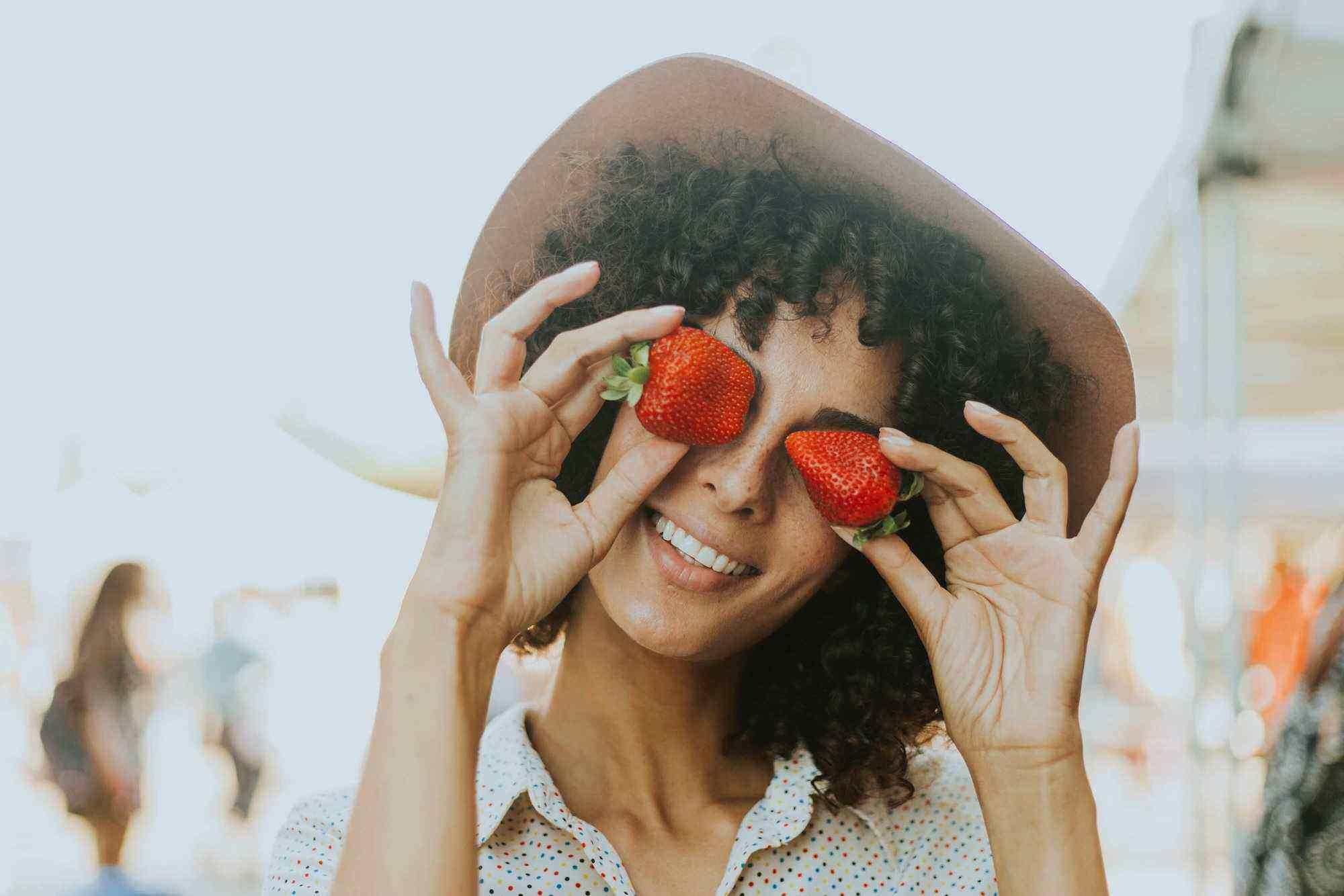 Lady with curly hair and a hat smiling and holding strawberries to her eyes