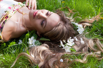 Woman lying across the grass with flowers in her hair