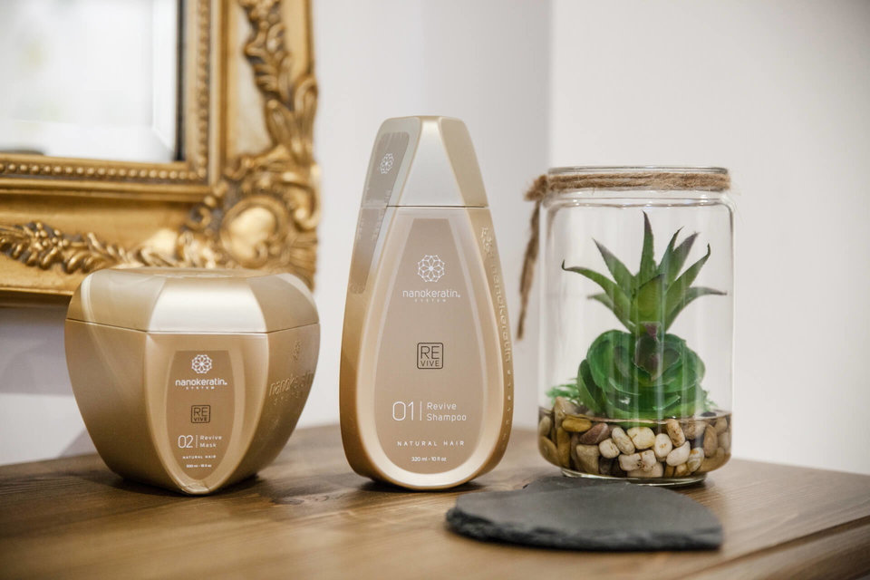Gold Nanokeratin Aftercare Bottles with a plant in next to it